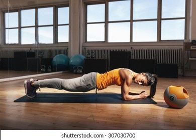 Young muscular woman doing core exercise on fitness mat in the gym. Fit female doing press-ups during the training in the health club.