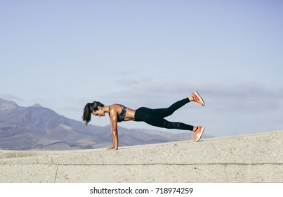 Young muscular woman doing core exercise outdoors. Fit female doing press-ups during training session. Side view shot.