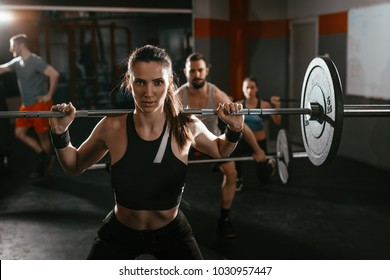 Young muscular woman doing exercise with barbell at the gym. Looking at camera. Behind her there are here friends exercising.