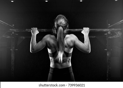 Young muscular woman doing pull up exercise on horizontal bar. Fit female practicing strength training. Fitness, sports concept.