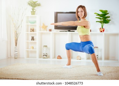 Young muscular woman doing some squat exercises at home in her living room.