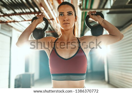 Young muscular woman exercise kettlebells on stock photo edit now