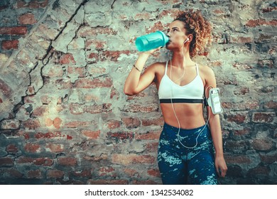 A young muscular woman, with headphones, is standing up against the wall and drinking water after training.