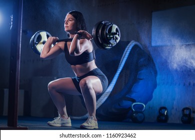 Young muscular Woman Workout with Barbell at gym. Girl doing squat exercises with weight bar. Fitness training.