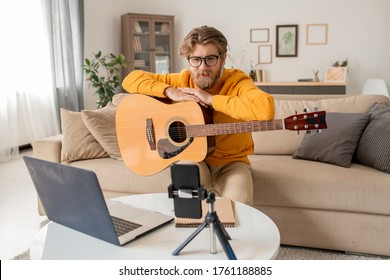 Young music teacher talking to his audience during online lesson of playing guitar while sitting on couch in front of smartphone camera