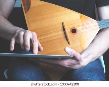 Young musician with a balalaika using a tablet computer