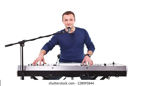Young musician behind synthesizer and microphone preparing for concert