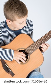 Young musician boy with classic wooden guitar.