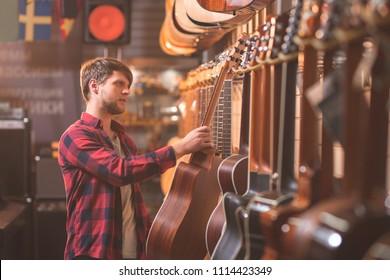 Junge Musikerin wählt eine Gitarre in einem Musikgeschäft