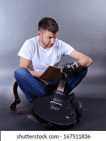 Young musician creating new melody for guitar on gray background
