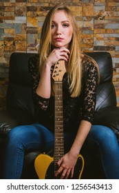 Young musician girl in blue jeans and black lace shirt sitting in chair and posing with guitar on brick background