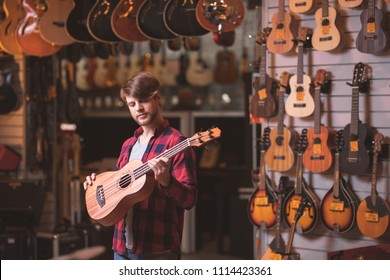 Young musician with a guitar in a music store
