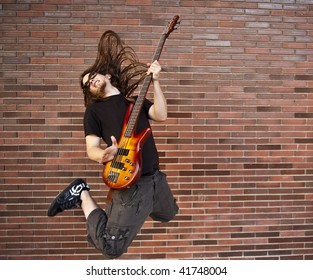 Young musician jumping against brick wall
