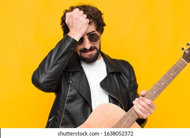 young musician man feeling stressed and anxious, depressed and frustrated with a headache, raising both hands to head with a guitar, rock and roll concept