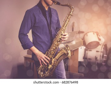 young musician man plays tenor saxophone on stage with light bokeh effected over  blurred music instrument background