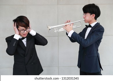 young musician man wearing black suit making too loud music and annoying from trumpet to his friend