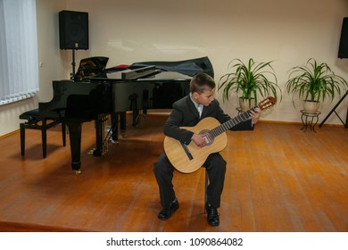 A young musician performs a musical work on classical guitar at the exam at a music school. Zaporozhye region, Ukraine. November 2011