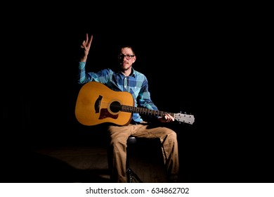 Young musician in plaid shirt playing the guitar and singing on dark background.