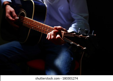 Young musician playing acoustic guitar, close up, on dark background