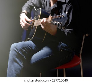 Young musician playing acoustic guitar on dark background