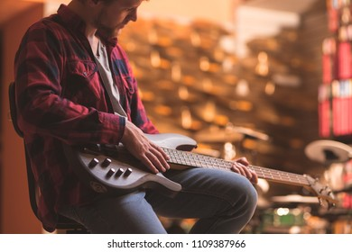 Young musician playing bass guitar