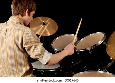 Young musician playing drums isolated on black.