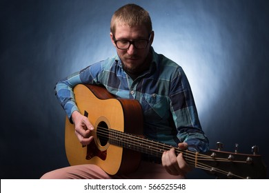 Young musician playing the guitar on dark blue background