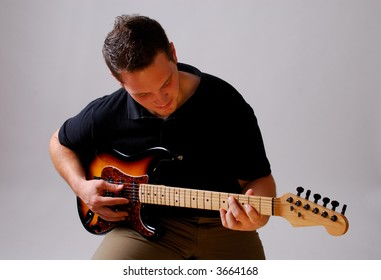 Young Musician Playing An Older Style Lead Guitar, Isolated On A Grey Background