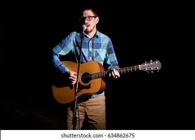 Young musician playing in plaid shirt playing the acoustic guitar and singing.