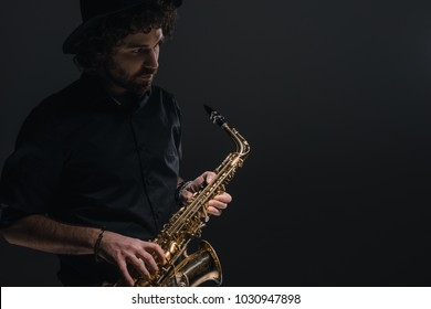 young musician playing saxophone on black