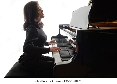 Young musician plays the grand piano, silhouette image isolated on white background