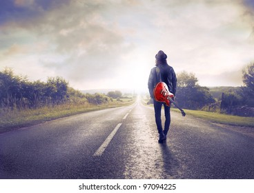 Young Musician Walking On A Countryside Road With Guitar His Shoulder