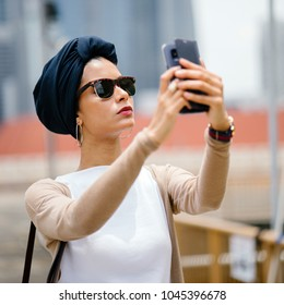 A young Muslim Arab woman takes a selfie of herself with the city skyline of Singapore in the background. She is elegant, tall, slim and wearing a turban (hijab) and is smiling as she takes her photo.