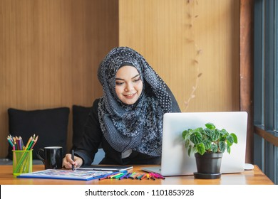 Young muslim asian female designer using graphics tablet while working with computer at studio or office.