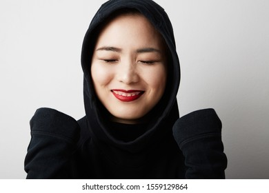 Young muslim asian woman posing on the white background and smile. Isolated.