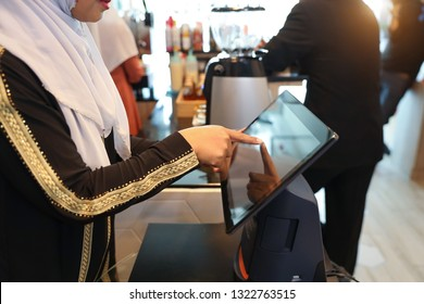 young muslim barista girl working at cashier counter by touching computer screen