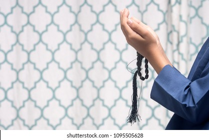 Young muslim boy prayer during holy month of Ramadhan with rosary beads in hand.
