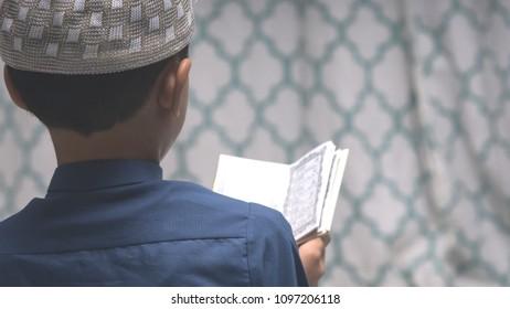Young muslim boy reciting Koran during the holy month of Ramadan