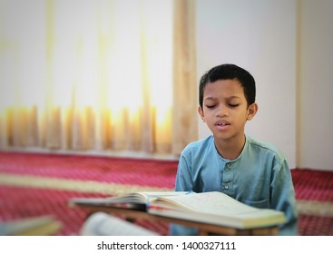 Young muslim boy reciting Quran in the holy month of Ramadan