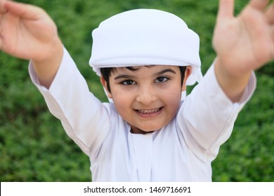 Young Muslim boy stretching and reaching his both arms on front while wearing kandura
