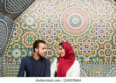 Young Muslim couple in relationship talking and smiling in front of arabesque oriental decoration