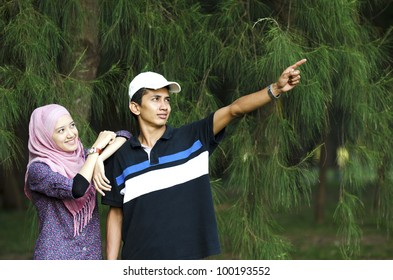 Young Muslim couple see at above on male pointing hand.