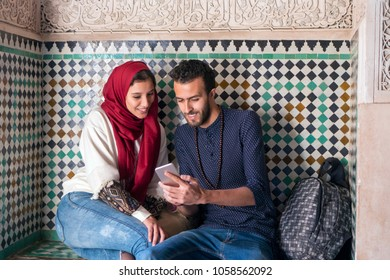 Young Muslim couple smiling and looking at mobile phone
