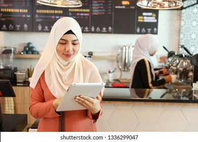 young muslim employee barista standing and using tablet at coffee shop counter with working colleague blurred background