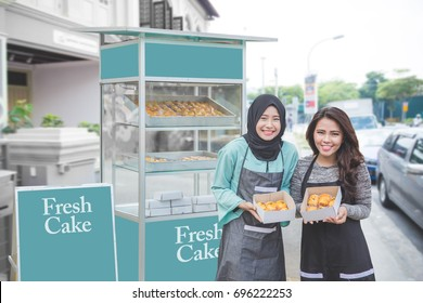 young muslim entrepreneur with her partner starting their business by opening small food stall