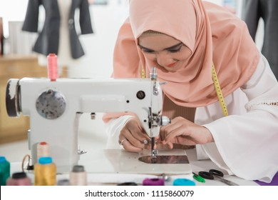 young muslim fashion designer using sewing machine in her workshop