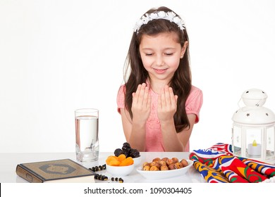 Young Muslim girl praying to Allah while waiting for iftar( breakfast ) in Ramadan