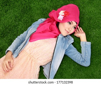 Young muslim girl wearing hijab lying on grass
