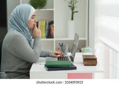 Young Muslim Girl Wotking on Laptop on Desk