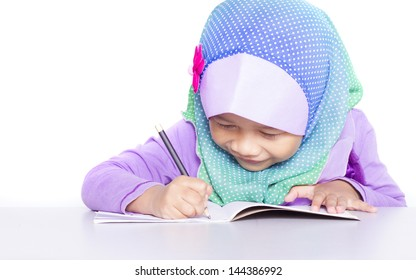Young muslim girl writing a book on the desk.  Isolated white background